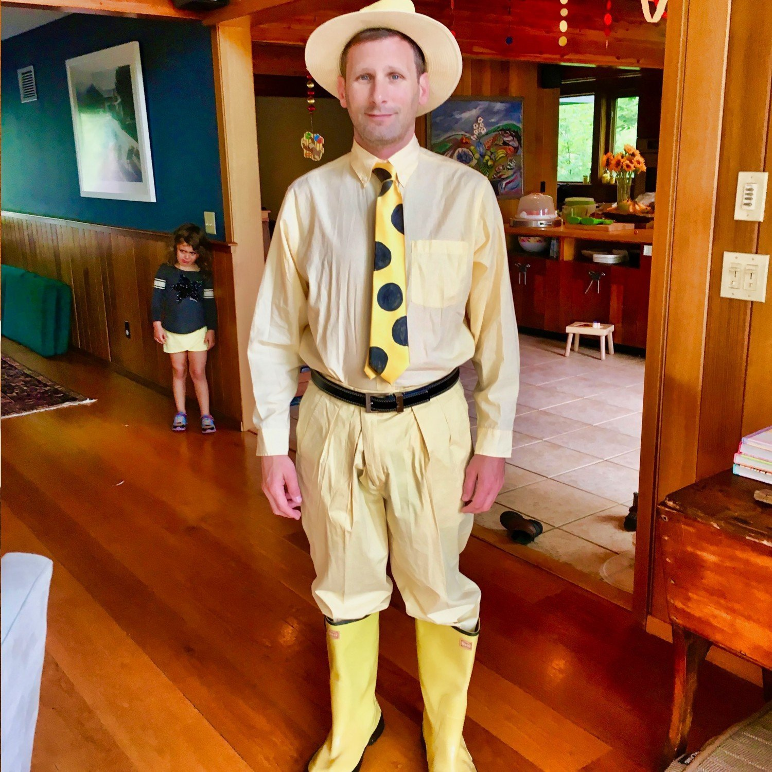 man dressed as the man in the yellow hat from curious george for party surprise