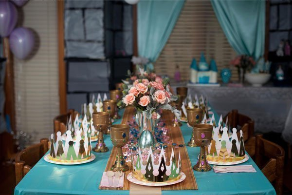 princess party decortations and tabletop setting with crowns, goblets and treat table