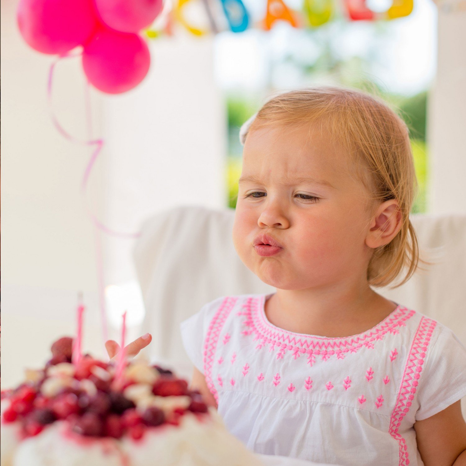 birthday girl blowing candles out at a birthday party