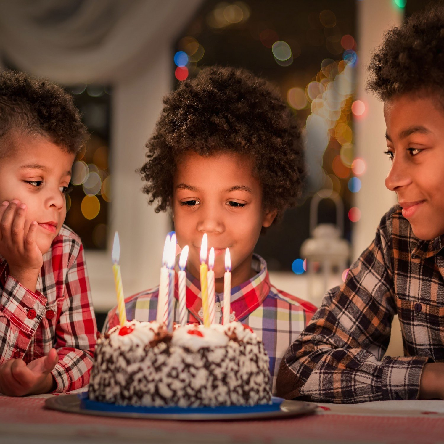 kids looking at candles on a birthday cake